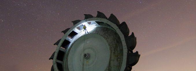 Schaufelrad eines Braunkohlebaggers vor dem Nachthimmel, ein Kletterer seilt sich daran ab.