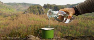 Felslandschaft, davor gießt jemand Wasser aus einer Glaskaraffe in einen Trinkbecher