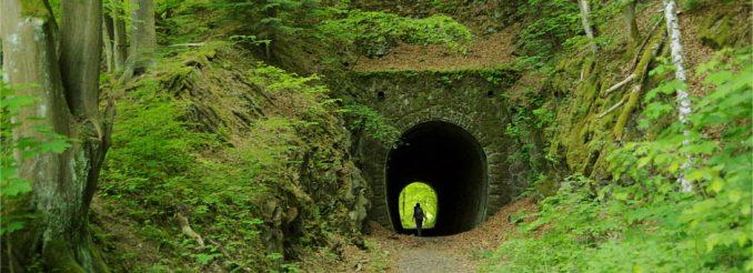Tunneleingang versteckt im Wald - am Ende des Tunnels Licht und eine Wanderin.