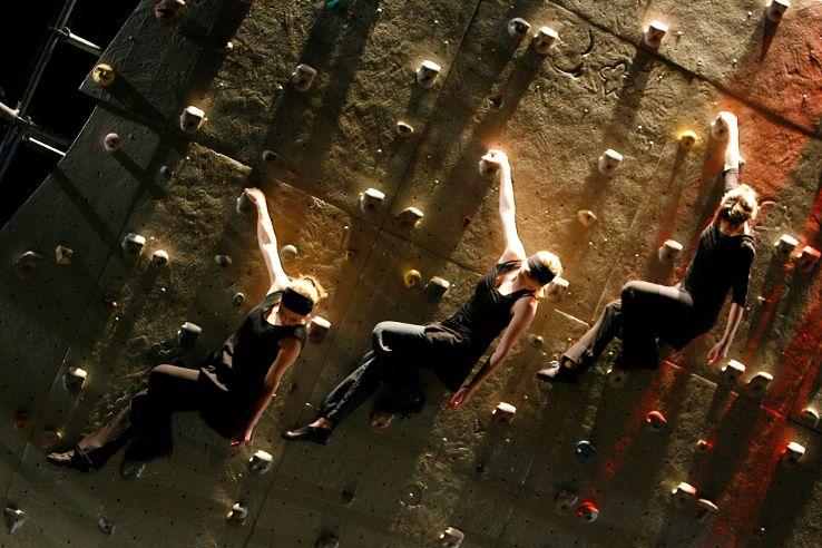 Drei Kletterer in aufeinander abgestimmten Bewegungsformen an der Wand