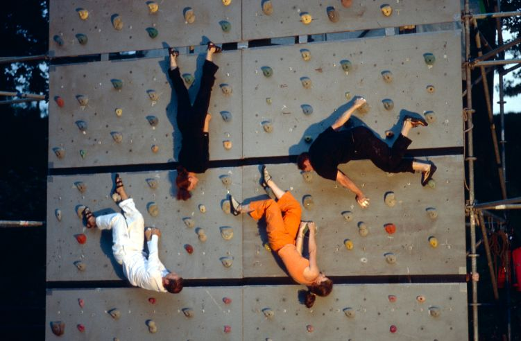 Vier Kletterer an einer Kunstwand - teils kopfüber