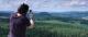Ein Mann peilt mit einem Kompass einen Tafelberg am Horizont an.